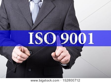 ISO 9001 written on virtual screen. technology, internet and networking concept. man in a business suit and tie holds a PC tablet.
