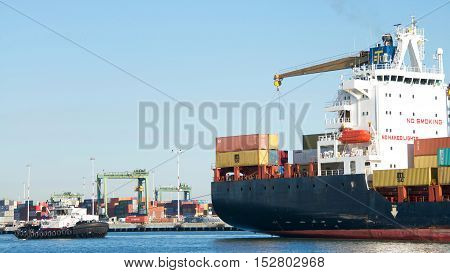 Oakland CA - September 26 2016: Tugboat REVOLUTION at the stern of Cargo Ship NIKOLAS assisting the vessel to maneuver into the Port of Oakland.