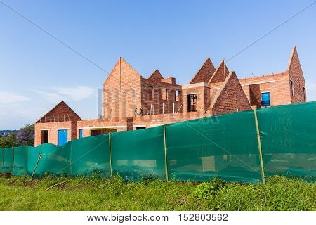 House building construction halfway brickwork structure in blue sky