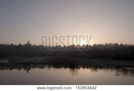 Winter morning landscape with reflection in the lake and upcoming sun