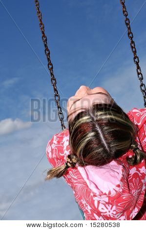 Freckle faced girl happy on the swing.