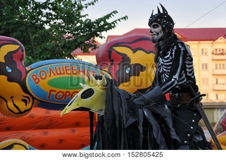 Grodno, Belarus - June 25, 2016: The city festival of street art in Grodno in June 2016. Actor in black suit with skeletal figure riding a stylized horse against the colorful children amusement park.