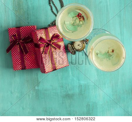 A photo of two glasses of champagne with gift boxes and a vintage chain clock. A New Year or Christmas greeting card on a teal background with copyspace. Selective focus on the rim of the glasses