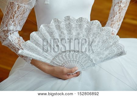 Young ballerina in white dress holding a white fan.