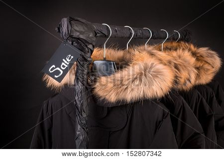 Sale Sign. A Lot Of Black Coats, Jacket With Fur On Hood Hanging  Clothes Rack.  Background.  Friday