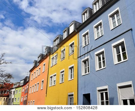 Street with old residential multistory houses of yellow orange blue colors in perspective against the blue sky. Lookup.