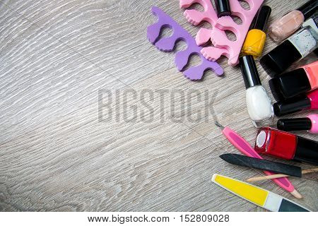 Set Of Nail Polish And Tools For Manicure  Pedicure  On A Grey Wooden Background. Frame. Copy Space.