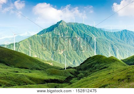 There are wind turbines that generate electricity and green mountains.