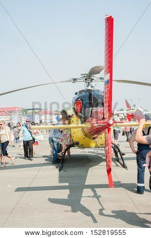 Tyumen, Russia - August 11, 2012: Air show On a visit at UTair in heliport Plehanovo. People explore Eurocopter AS-355NP Ecureuil 2