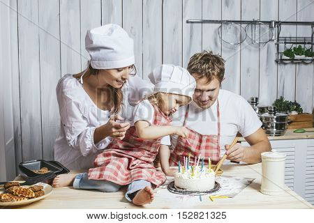 Family, Happy Daughter With Mom And Dad At Home In The Kitchen Laughing And Baking A Birthday Cake T