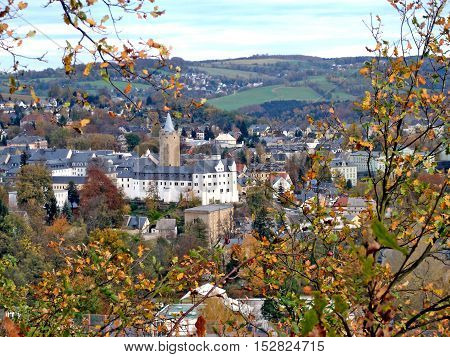 The town Zschopau in Erzgebirge in Saxony, Germany in fall,  in the middle of the houses the castle Wildeck, on the hills small villages, autumn landscape