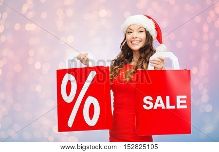 christmas, holidays and people concept - smiling young woman in santa hat holding red shopping bags with percent and sale sign over rose quartz and serenity lights background