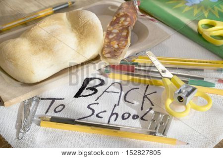 concept of back to school with some scholastic tools and a snack
