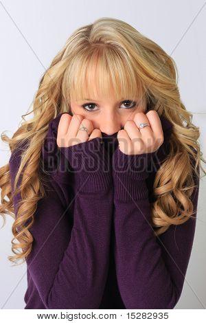 Cute blond girl hiding her face.