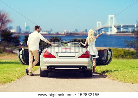people, travel, tourism and road trip concept - happy man and woman near cabriolet car over river and tokyo rainbow bridge background