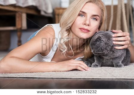 Best friends. Pretty blond-haired woman lying on floor and patting her favorite grey cat.