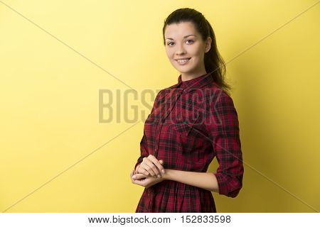 Side view of young woman in red checkered dress standing with her arms crossed against yellow background and smiling. Mock up