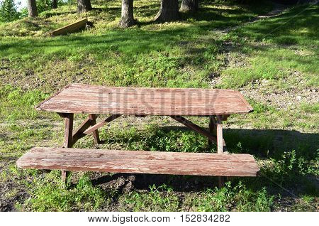 Weathered and worn old rustic picnic table for picnic style eating in the park on a sunny summer day