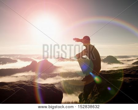 Flare. Strong lens defect reflections. Man in sportswear is sitting on cliff's edge and looking to misty valley bellow. Autumn landscape. Foggy mountain. Man hike poster