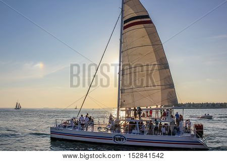Key West, Florida, United States - April 13, 2012: people enjoy for the Sunset Celebration on a sailing ship left from the pier at Mallory Square in Key West.