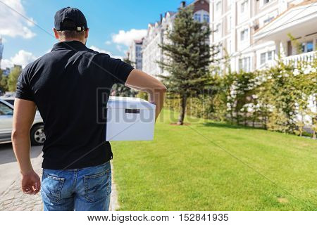 back view of a guy from delivery service walking on the street with copy space