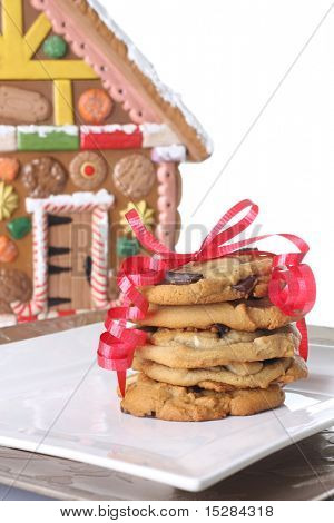 Christmas cookies in front of a gingerbread house cookie jar.
