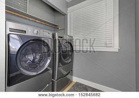 Laundry Interior With Gray Walls, Carpet And Modern Appliances.