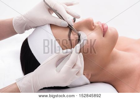 Close up of young woman lying and getting eyelash extension procedure by cosmetician