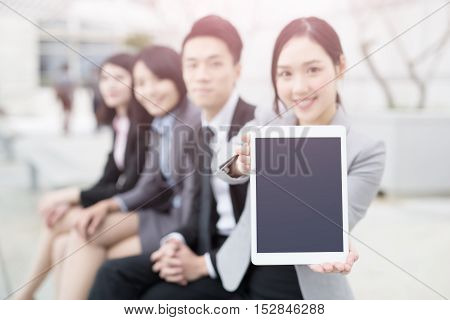 businesspeople show tablet to you in office in hongkong