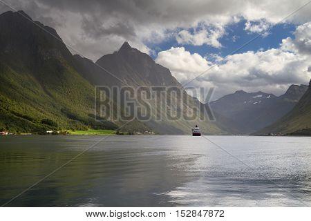 Cruiser at dramatic landscape Hjorundfjord, Fjordland, Norway