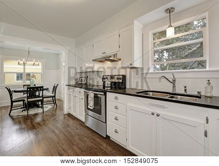 White Kitchen Storage Combination And Steel Appliances