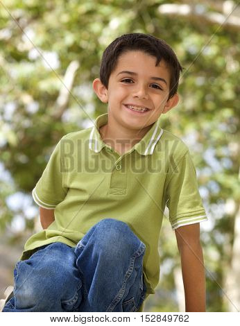 Portrait of a cute Little Boy outside with blurred leaves in the background.