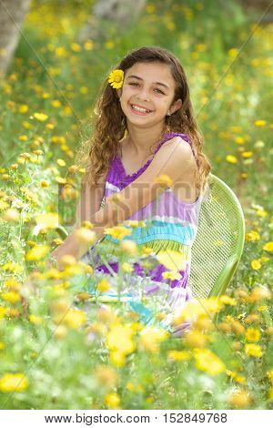 Beautiful twelve year old girl in a field of yellow wild flowers.  She is smiling and has a flower in her hair.
