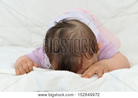 Tired baby girl lying on her stomach and sleeping