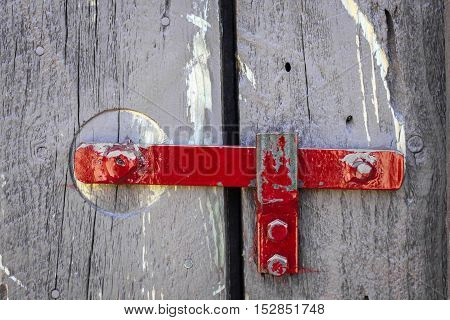 horizontal image of a close up shot of a bright red steel latch on grey wood barn doors