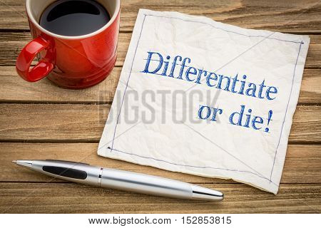 Differentiate or die!  Handwriting on a napkin with a cup of espresso coffee