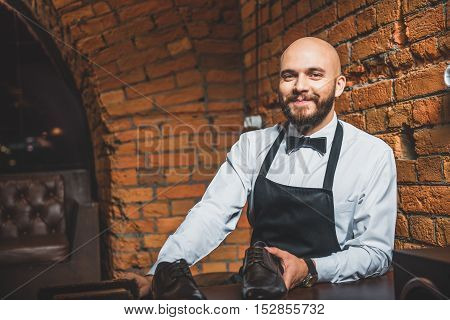 smiling shoe shiner holding a footwear and looking into camera indoors