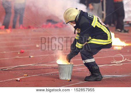 Sofia Bulgaria - October 15 2016: Firefighter is putting down football fans' fire from torches during a match between Bulgaria's CSKA and Levski.