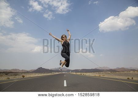 young lady jumping in the middle of an Empty road in remote Oman