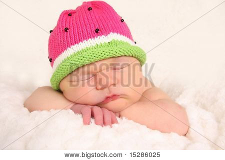 Newborn baby girl, asleep wearing a knitted hat.