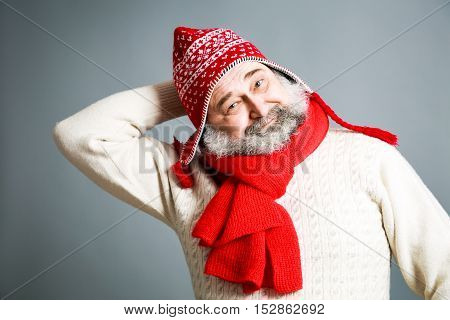 Portrait of Happy Old Man with Beard in Red and White Winter Clothes on Gray Background. Modern Mature Man Concept. Copy Space.