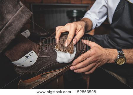 man gets his shoes polished by an artificer using a wet sponge and a wooden shoe platform