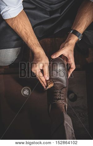 hands of an artificer wiping the shoes of a man, top view