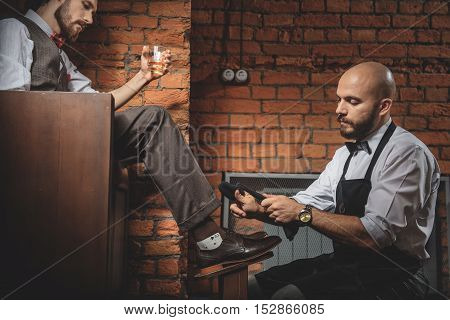 man drinking whiskey and watching how shoe shiner working with his shoes