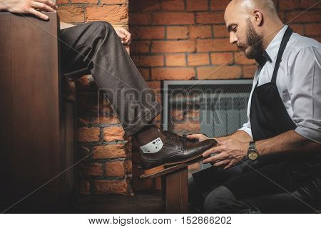 professional shoe shiner correcting footwear of the man, side view