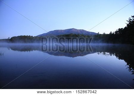 blue lake with trees on a hazy morning overlooking Mt. Katahdin