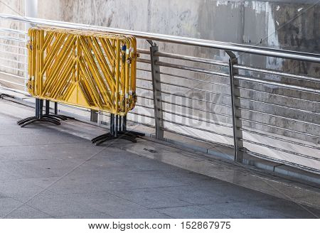 The Group of yellow barrier near the rail of the sky bridge.