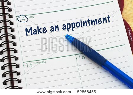 Reminder to make an appointment A day planner with blue pen with text Make an appointment
