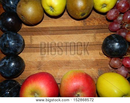 Along the perimeter of the wooden planks laid out plums, pears, apples, grapes