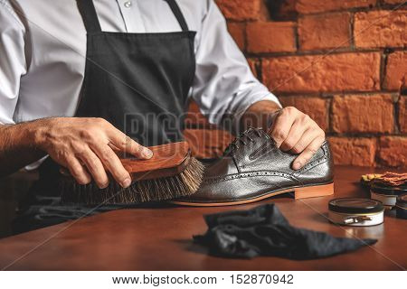close up of a man brushing leather shoes on the desk